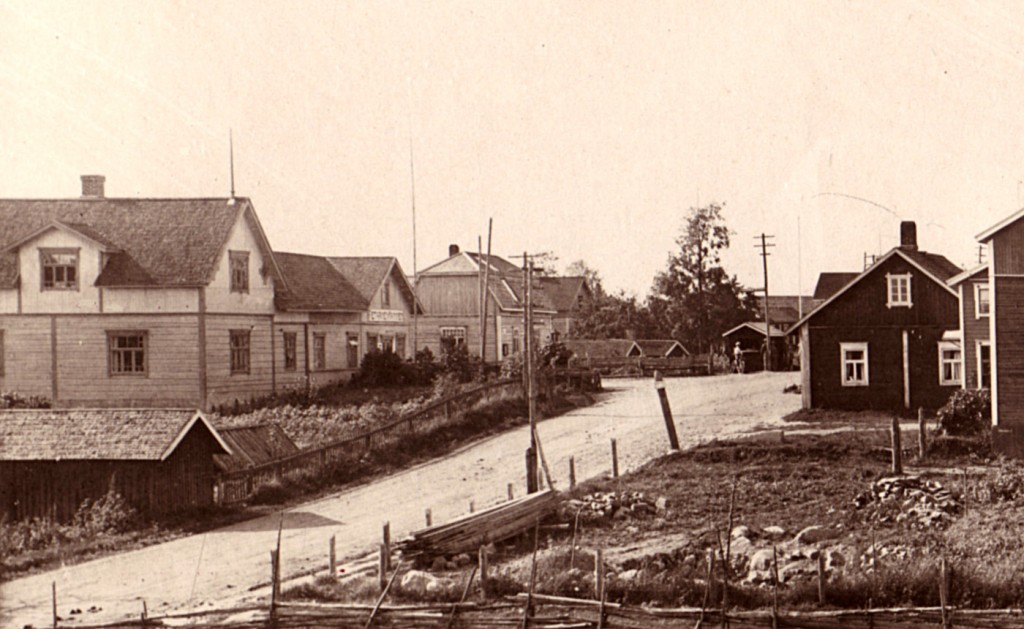 1920-luvulta olevassa kuvassa on sama rakennus varhaisemmassa asussa. Toiminimi Pietarinen&Manninen harjoitti talossa sekatavarakauppaa. Vihtori Mannisella oli kauppa myös Puhoksessa, jonne hän sittemmin siirtyi kokonaan. Tämän talon tontti oli alun perin lukkarin puustellin maata, kun taas Pietarinen sai lunastetuksi torpan paikan  tien vastakkaiselta puolelta Romolan virkatalon alueelta.